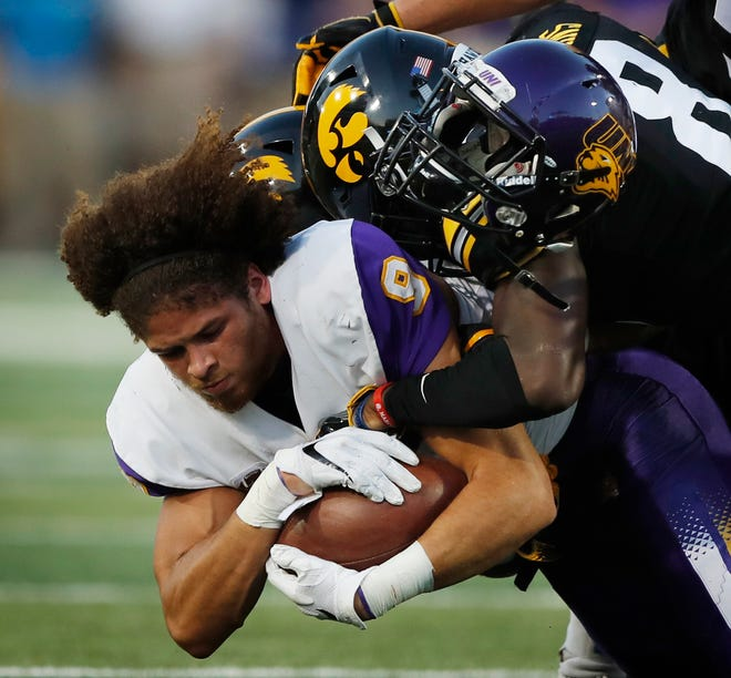 Northern Iowa's Xavior Williams (9) loses his helmet as he is tackled by Iowa's Matt Hankins (8) while returning a kickoff during the first half of an NCAA college football game, Saturday, Sept. 15, 2018, in Iowa City, Iowa. (AP Photo/Charlie Neibergall)