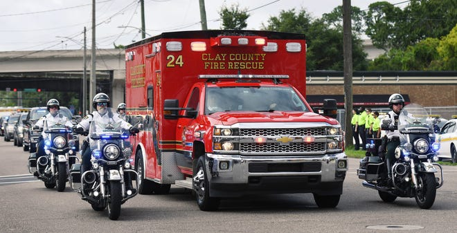 Clay County motorcycle officers escort the ambulance carrying the body of Sgt. Eric Twisdale who died from COVID-19. He was transported to a Jacksonville funeral home Thursday as members of the Jacksonville Sheriffs Office and Jacksonville Fire and Rescue lined Park Street as the motorcade finished its journey.
