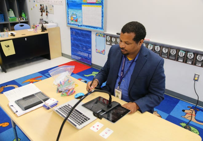 LCPS teacher Ramon Jones shows how he uses Cuisenaire rods and playing cards to teach counting and math through remote learning Monday, August 17, at La Grange Elementary School on the first day of remote learning. [Brandon Davis/Kinston Free Press]