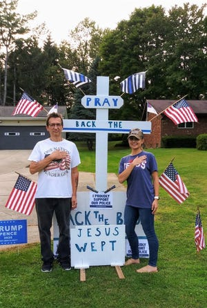Stow resident Chris Caetta and Gina Brown stand in front of a cross in front of Caetta's Marsh Road home Sept. 16. While driving past Caetta's home shortly after someone knocked the cross over on Aug. 4,