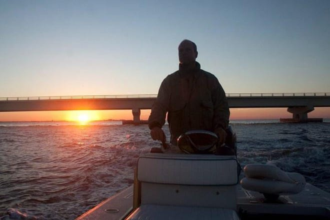 Capt. Dave Torrance of Fort Myers pilots his flats fishing boat as he searches for bait to cast net west of San Carlos Bay as the sun rises over the Sanibel Causeway.