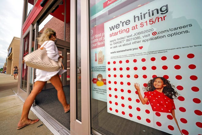 In this Sept. 2 file photo, a help wanted sign hangs on the door of a Target store in Uniontown, Pa. Hundreds of thousands of Americans likely applied for unemployment benefits last week, a high level of job insecurity that reflects economic damage from the coronavirus outbreak. Economists expect that 850,000 people sought jobless aid, down from 884,000 the week before, according to a survey by the data firm FactSet.