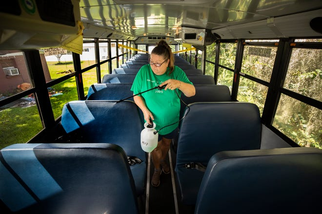 Polk County Public Schools bus driver Margie Patterson sprays disinfectant throughout the seating area in her bus. Bus drivers are having to clean their buses between each route and fill in at schools, handing out lunches and making copies for teachers, but haven't been told in the last month about any positive COVID-19 cases they have come in contact with.