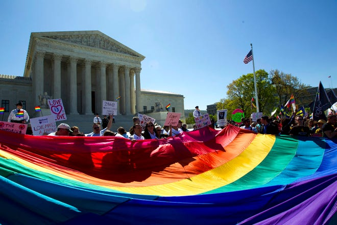 In this April 28, 2015, file photo, demonstrators stand in front of a rainbow flag of the Supreme Court in Washington. In 2019, there were slightly less than 1 million same-sex couple households in the U.S., and a majority of those couples were married. New figures released Thursday by the U.S. Census Bureau shows that of the 980,000 same-sex couple households, 58% were married couples and 42% were unmarried partners.