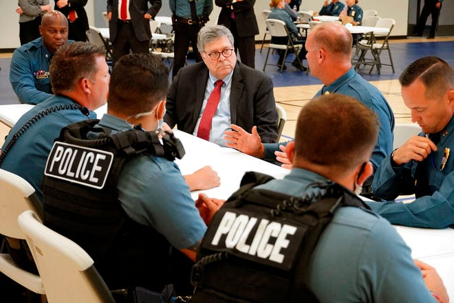 In this Aug. 19 photo, Attorney General William Barr participates in a roll call with police officers from the Kansas City Police Department in Kansas City, Mo. In a private conference call this week with his U.S. attorneys nationwide, Attorney General William Barr said he wanted prosecutors to be aggressive in charging demonstrators who cause violence.