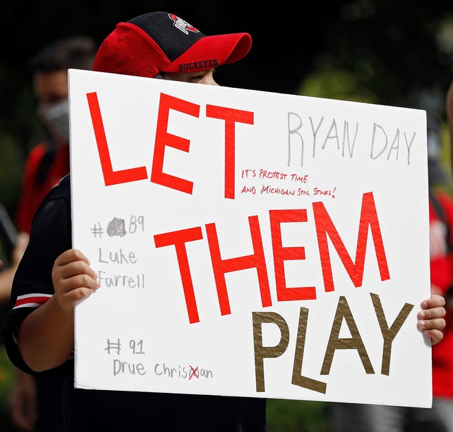 A young fan holds up a sign during a rally organized by parents of Ohio State football players in August.