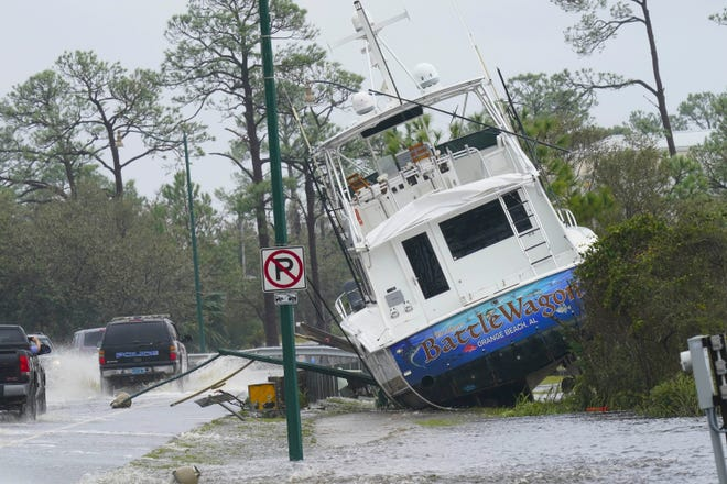 A boat is washed up near a road after Hurricane Sally moved through the area, Wednesday in Orange Beach, Ala. Hurricane Sally made landfall Wednesday near Gulf Shores, Alabama, as a Category 2 storm, pushing a surge of ocean water onto the coast and dumping torrential rain that forecasters said would cause dangerous flooding from the Florida Panhandle to Mississippi and well inland in the days ahead. [GERALD HERBET/Associated Press]