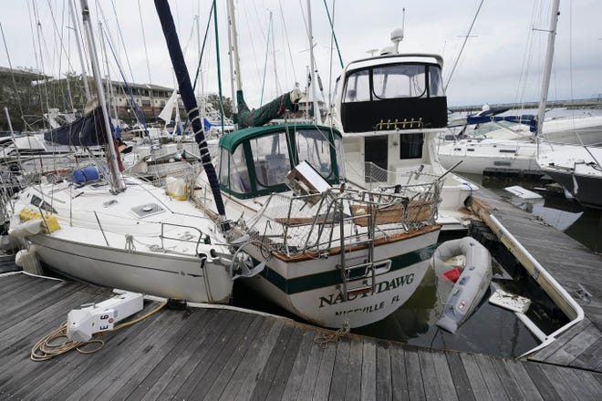 Storm damaged boats sit at the dock in a marina, Thursday in Pensacola. Rivers swollen by Hurricane Sally's rains threatened more misery for parts of the Florida Panhandle and south Alabama on Thursday, as the storm's remnants continued to dump heavy rains inland that spread the threat of flooding to Georgia and the Carolinas. [GERALD HERBET/Associated Press]