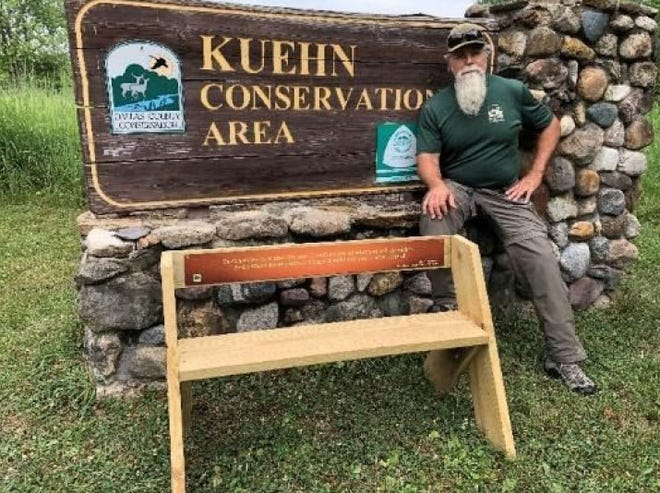 """Chris Adkins, Dallas County Conservation Board naturalist, showcases a Leopold Bench in front of the Kuehn Conservation area sign. This photo was part of a clue for participants in the """"Where's Aldo?"""" Leopold Bench scavenger hunt."""