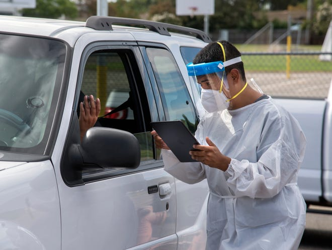 Medical assistant Hector Loya with Carbon Health takes down information at a free coronavirus testing event Aug. 14 sponsored by El Concilio at the First Baptist Church in Lodi.