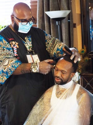 Big Herk, 52, of Big Herk's Clippers gives a haircut to Bobby Wyatt home in Wyatt's south Stockton home.