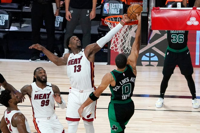 Miami's Bam Adebayo (13) blocks a shot attempt by Boston's Jayson Tatum in the closing seconds of overtime of Tuesday's game as Jimmy Butler and Jae Crowder (99) look on. Miami won the opening game of the Eastern Conference finals with the two teams playing Game 2 on Thursday.