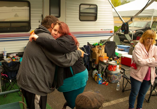Fred Heins, left, glives Kami Hayes a hug Thursday as they join other residents of Blue River who have been displaced by the Holiday Farm Fire in the parking lot of the Holiday Inn Express in Eugene.