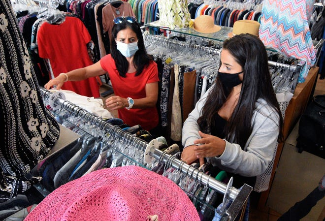 Adrianne Pezzella and her daughter Sienna, 15, browse the jacket section at SPARCC Treasure Chest in downtown Sarasota on Thursday.  The thrift store has become a more crucial source of income for Sarasota's Safe Place and Rape Crisis Center with the usual fundraising events canceled amid the pandemic.