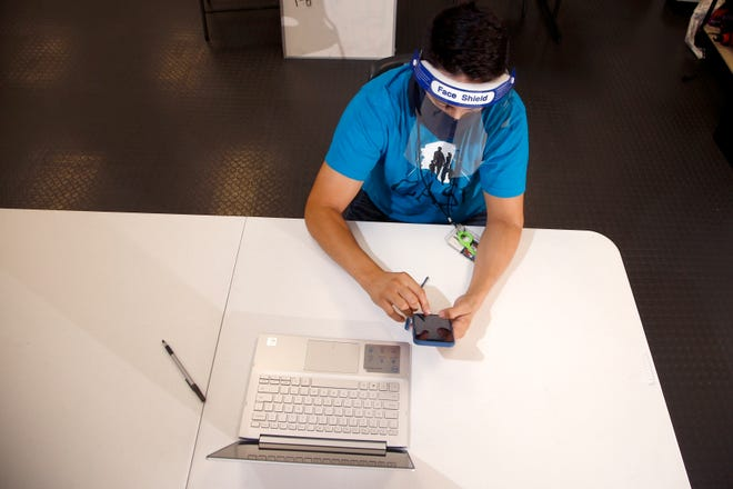 While wearing a face covering and shield due to the coronavirus, a voter registration organizer works his phone and computer as he tries to reach people to help them register to vote.