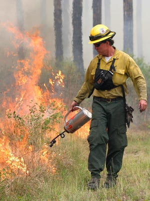 Vic Doig, who was named the 2020 National Wildlife Refuge System Employee of the Year by the National Wildlife Refuge Association, lights a prescribed fire.