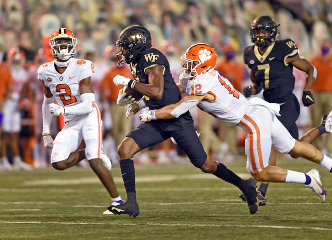 Clemson's Tyler Venables, right, reaches out to tackle Wake Forest receiver Jaquarii Roberson.