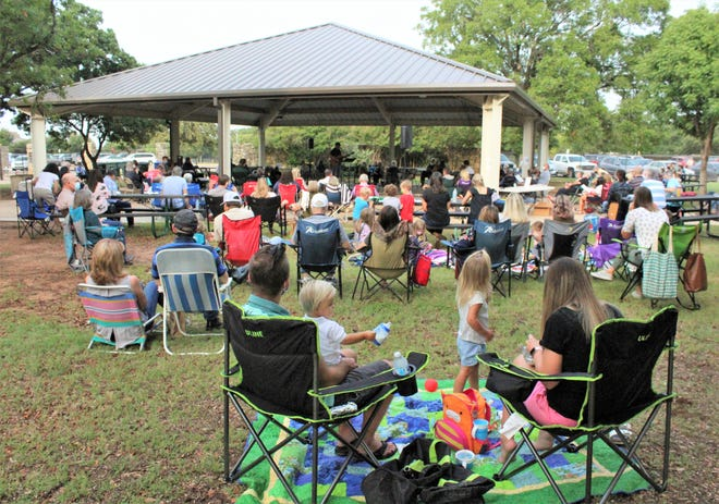 Those attending the first Highland Church of Christ Sunday service at the Nelson Park Festival Gardens spread out with chair and blankets.