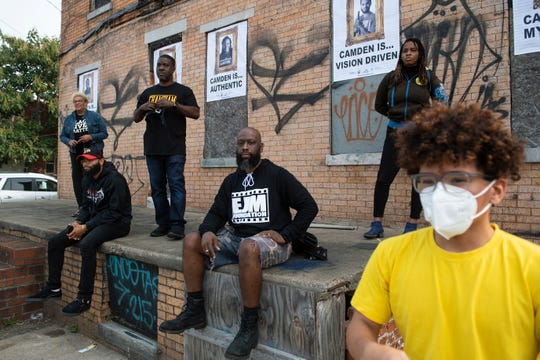 Erik James Montgomery, center, pictured with a group of his subjects for his his art installation 'Camden Is Bright Not Blight' Wednesday, Sept. 16, 2020 in Camden, N.J.
