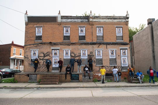 Subjects depicted in Erik James Montgomery's art installation 'Camden Is Bright Not Blight' pose with the project Wednesday, Sept. 16, 2020 in Camden, N.J.