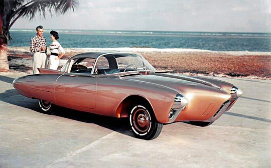 "The Oldsmobile Golden Rocket was shown at the 1956 Motorama with a gold-colored fiberglass body, brilliant blue interior and aerodynamic styling.  The Golden Rocket (XP-400) possessed a look of both grace and swiftness. Although it was less than 50 inches tall, driver and passenger could easily enter and exit the vehicle. As one of the doors opened, a roof panel was raised, and the seat was elevated and rotated outward. To aid the driver's entry, the car also featured a folding steering wheel, which would release when two buttons were pressed. Golden RocketÕs front wheels were housed in ""twin torpedo"" pontoons flanking a slim aircraft-inspired streamlined engine enclosure."
