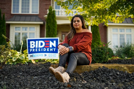 Aditi Bagchi of Northville, a dentist and mother of two, sits next to a sign endorsing Joe Biden for president in front of her home in Northville on Wednesday, September 16, 2020.