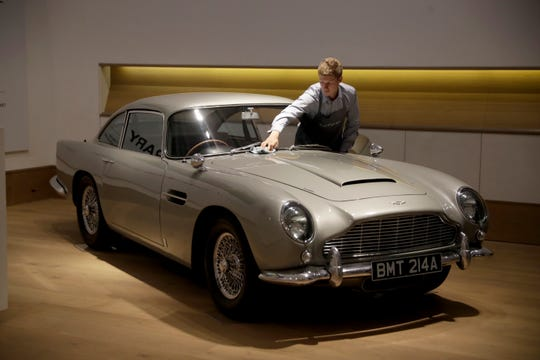 "A staff member from the Bonhams motor car department poses for photographers with the 1965 Aston Martin DB5 driven by actor Pierce Brosnan in his role as James Bond in the 1995 movie ""GoldenEye"" during a photo call at Bonhams auction house in London, Tuesday, June 19, 2018. The car is estimated to fetch between 1.2 million and 1.6 million pounds ($1.6 million to $2.1 million, 1.4 million to 1.8 million euro) in a sale on July 13. (AP Photo/Matt Dunham)"