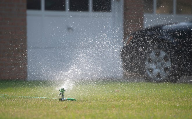A sprinkler waters a lawn along East Locust Street in Fort Collins, Colo. on Thursday, Sept. 17, 2020.