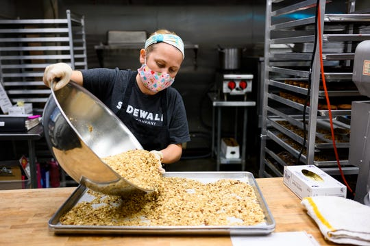 Pastry cook Makesha Duncan spreads walnuts on a pan at Sidewall Pastry Kitchen Wednesday, Sept. 16, 2020.