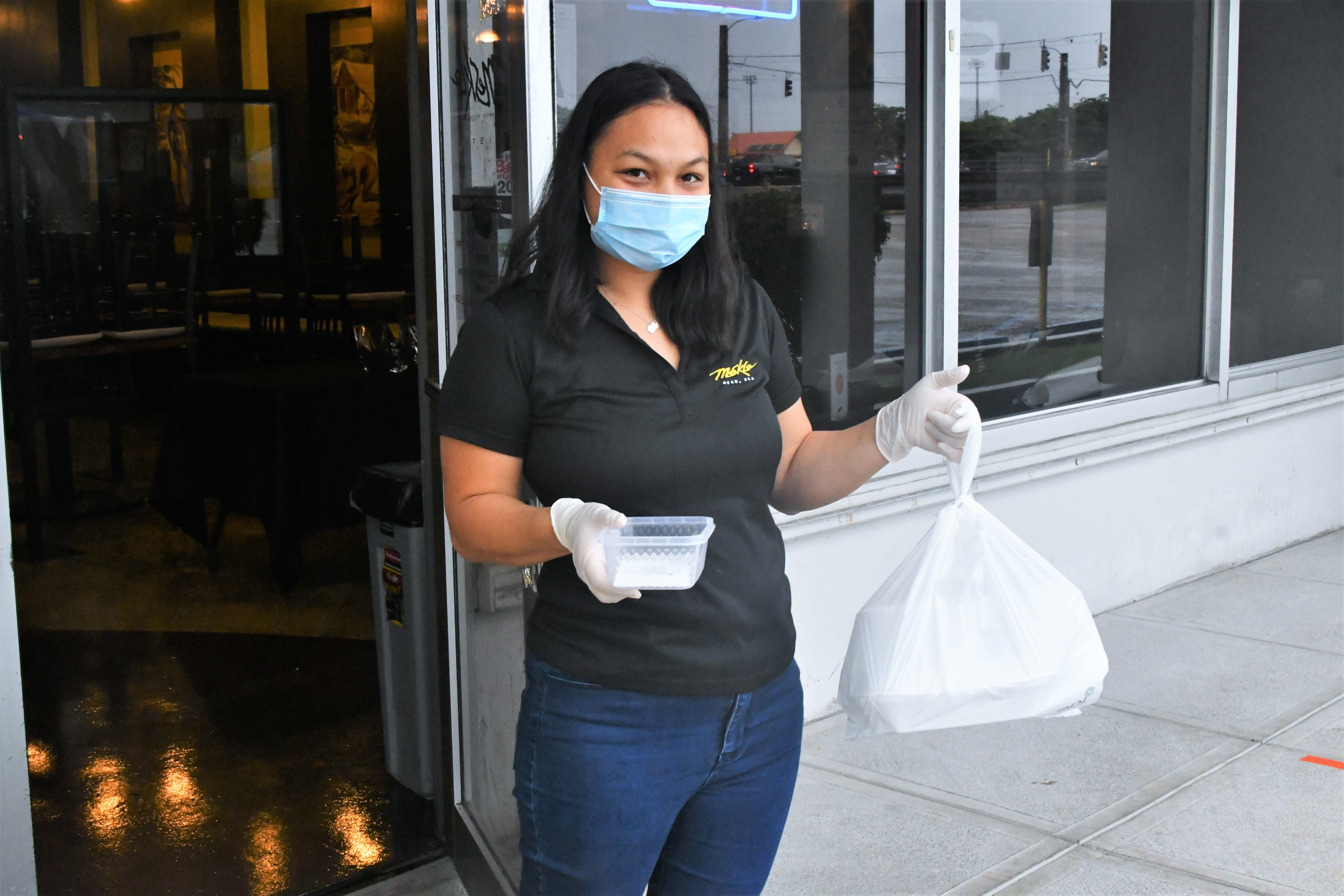 Breanalyn Edwards smiles as she heads out of the Meskla Chamoru Fusion Bistro to deliver food to customers in the parking lot on Sept. 16, 2020.