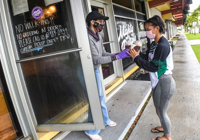 Dededo resident Elisha Benavente, right, accepts her call-in acai order from Mighty Purple barista Missy Sanchez at the entrance of the Hagåtña business on Tursday, Sept. 17, 2020. Beginning at noon Friday, restrictions are slated to be lifted that would allow customers into eateries solely for the purpose of receiving their orders.