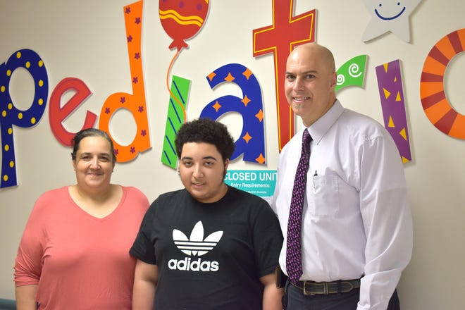 Dyllyn Leger, 15, center, poses for a photo outside the Pediatrics department at Our Lady of Lourdes Women's & Children's Hospital with Dr. Ryan P Farmer, right, and Karen Leger, left, his mother, after his recent scoliosis surgery.