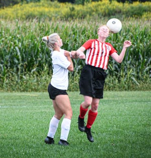 LIberty Union's Rachel Miracle deflects the ball away from a New Lexington defender during their non-conference match. The Lions won 7-0.