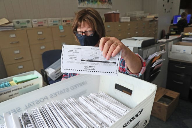 Linda Golembiewski places ballots in envelopes to be mailed out from the clerk's office in Wauwatosa City Hall on Sept. 17. Volunteers fold and sort ballots by hand before beginning to stuff envelopes and mail them out.