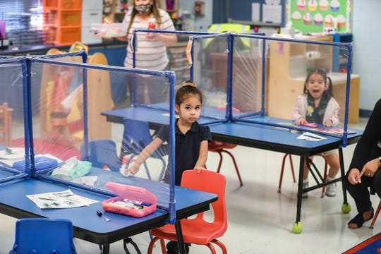 Younger students that are not legally required to wear masks have socially distanced desks with plastic barriers at Las Cruces Catholic School in Las Cruces on Thursday, Sept. 17, 2020.