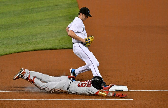 Boston Red Sox leadoff hitter Alex Verdugo (99) dives safely ahead of Miami Marlins starting pitcher Trevor Rogers (95) for a base hit in the 1st inning at Marlins Park on Sept. 16, 2020. Miami won, 8-4.