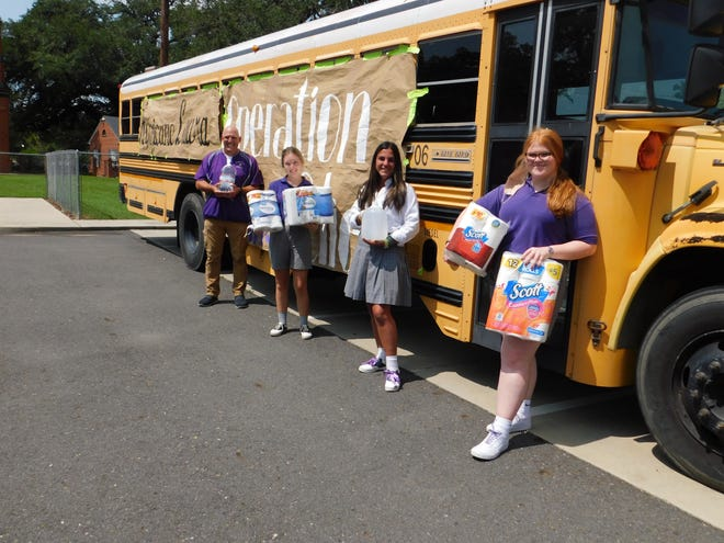 John Braham, who handles donations and campus ministry for Opelousas Catholic, stands with students Olivia Bragg, Aubry Hidalgo and Grace Bumell as they hold Hurricane Laura relief items for those in the Lake Charles area.