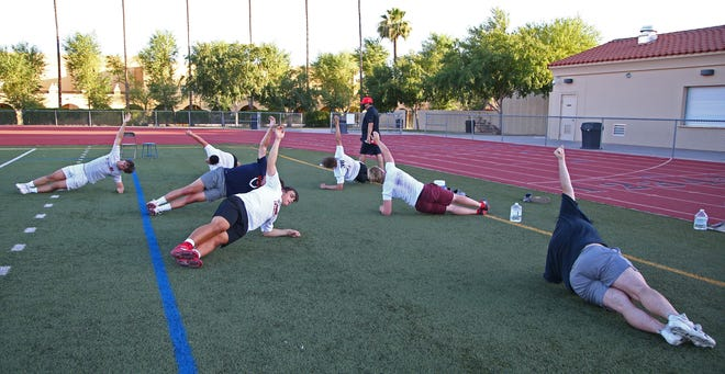 Jun 18, 2020; Phoenix, AZ, USA; Brophy College Preparatory football players perform a side plank during an ab routine. All 4 of the groups did the same routines. Mandatory Credit: Justin Toumberlin/The Arizona Republic via USA TODAY NETWORK