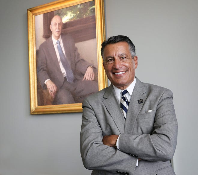 Governor Brian Sandoval poses for a portrait in front of a painting of past UNR President Joe Crowley after accepting the position of President of the University of Nevada, Reno on Sept. 17, 2020. Sandoval revealed that he took Political Science 101 from Crowley as a young student at UNR.