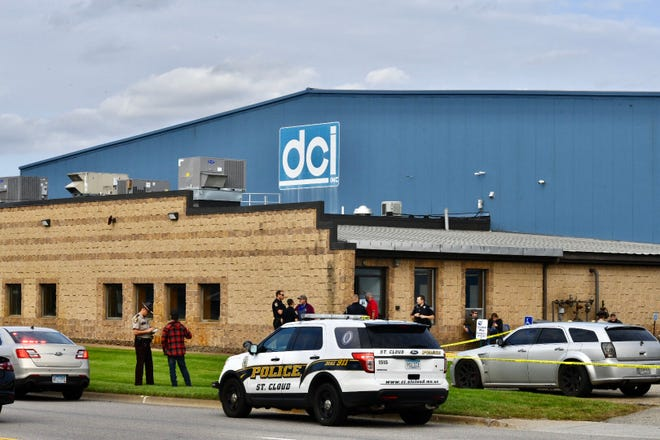 Law enforcement officers talk with people outside the entrance to DCI Inc. on Thursday,  Sept. 17, 2020 in St. Cloud.