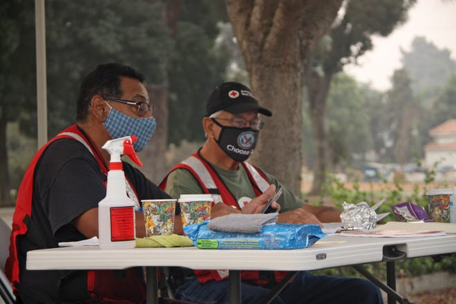 John Martinez (left) and Ray Quintana prepare for potential evacuees leaving the Three Rivers area. Both Martinez and Quintana are veterans volunteering their time to those in need.