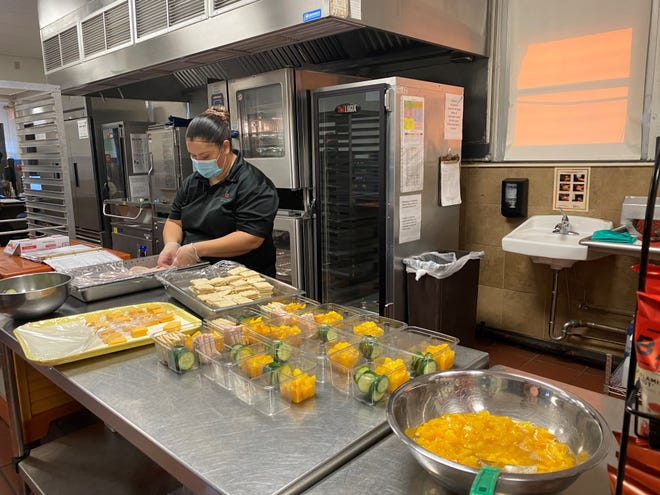 Maria Guiterrez, an associate for WFISD Chartwells K12, prepares food for a school meal.