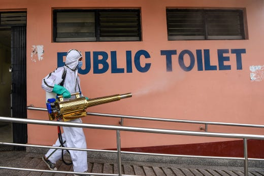 A worker wearing a Personal Protective Equipment (PPE) suit sanitizes public toilets at a bus station in Kathmandu on September 17, 2020.