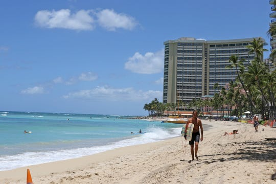 A surfer walks on a sparsely populated Waikiki Beach in Honolulu. Hawaii's governor says that starting Oct. 15, travelers arriving from out of state may bypass a 14-day quarantine requirement if they test negative for COVID-19.
