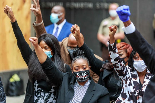 George Floyd's family raise their hands at a press conference outside the family justice center in Minneapolis on Sept. 11 after a court hearing.