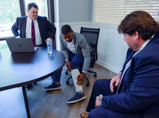 Jeffery Ryans points to his ankle as he talks about his encounter with the Salt Lake City police last month at his lawyer's office in Salt Lake City.  A Utah police officer was charged with aggravated assault after ordering his dog to attack Ryan, who had his hands in the air, prosecutors said Wednesday.  (Leah Hogsten / The Salt Lake Tribune via AP)