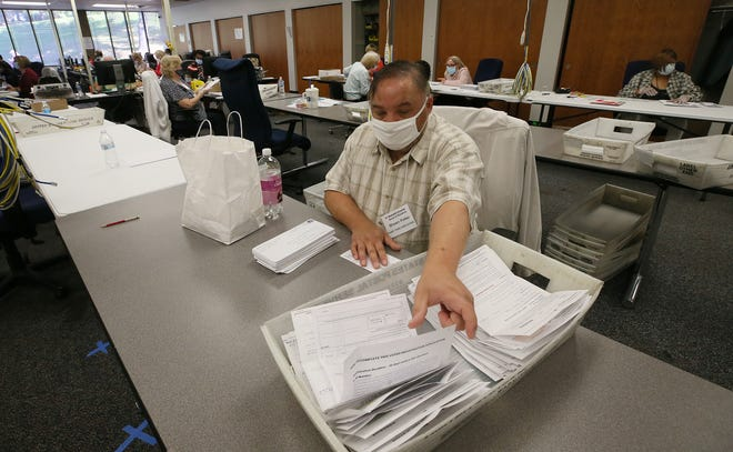 Shawn Potter, a part-time worker at the Summit County Board of Elections, sorts absentee ballot requests Friday at the board offices in Akron.