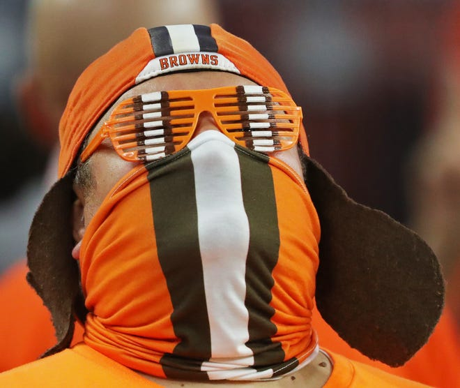 A masked Browns fan watches the action on the field during the second quarter of an NFL football game at FirstEnergy Stadium, Thursday, Sept. 17, 2020, in Cleveland, Ohio. [Jeff Lange/Beacon Journal]