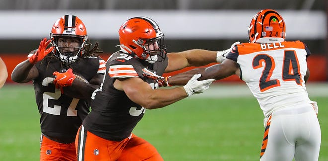 Browns fullback Andy Janovich blocks Cincinnati Bengals safety Vonn Bell as Browns running back Kareem Hunt rushes for a first down during the second half Thursday. [Jeff Lange/Beacon Journal]
