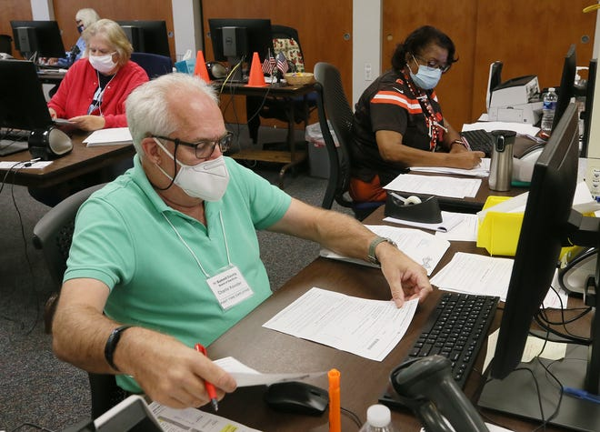 Charlie Koester and Vivian Farmer, part-time workers at the Summit County Board of Elections, check absentee ballot applications with voter records Friday at the board offices in Akron.